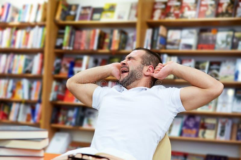 Vermoeide mens in de bibliotheek stock foto's