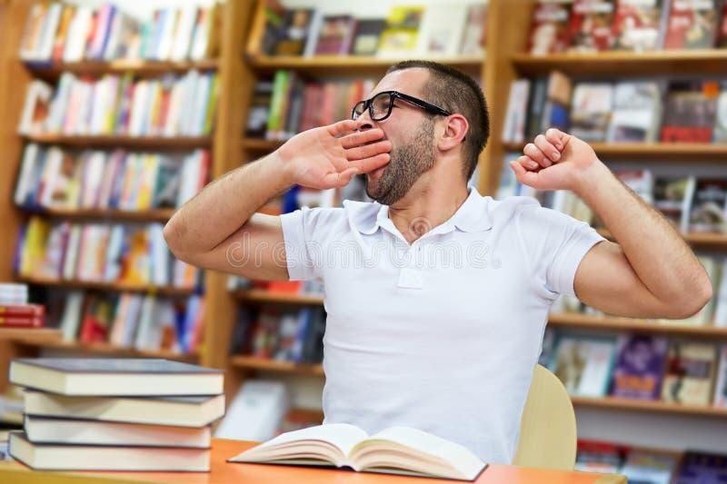 Vermoeide mens in de bibliotheek royalty-vrije stock foto's