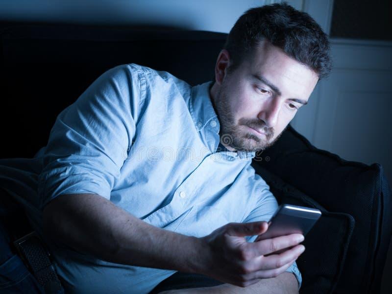 Vermoeide mens die aan zijn mobiele telefoon werken stock afbeeldingen