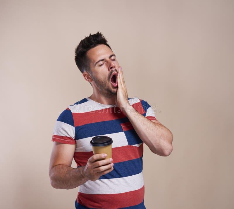 Vermoeide mens die en beschikbare kop van koffie houden geeuwen royalty-vrije stock afbeeldingen