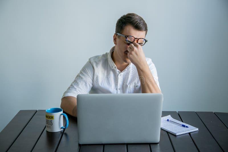 Vermoeide mens die in het bureau werken stock afbeelding
