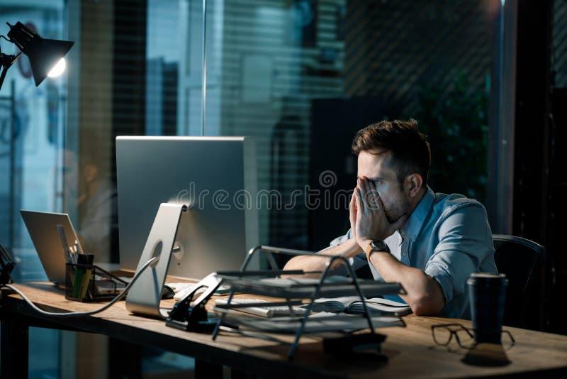 Vermoeide mens die in laat bureau werken royalty-vrije stock afbeeldingen