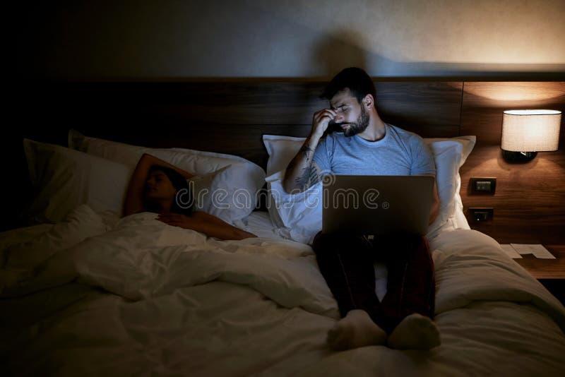Vermoeide mens die op bed liggen en met laptop laat bij nacht werken royalty-vrije stock afbeelding