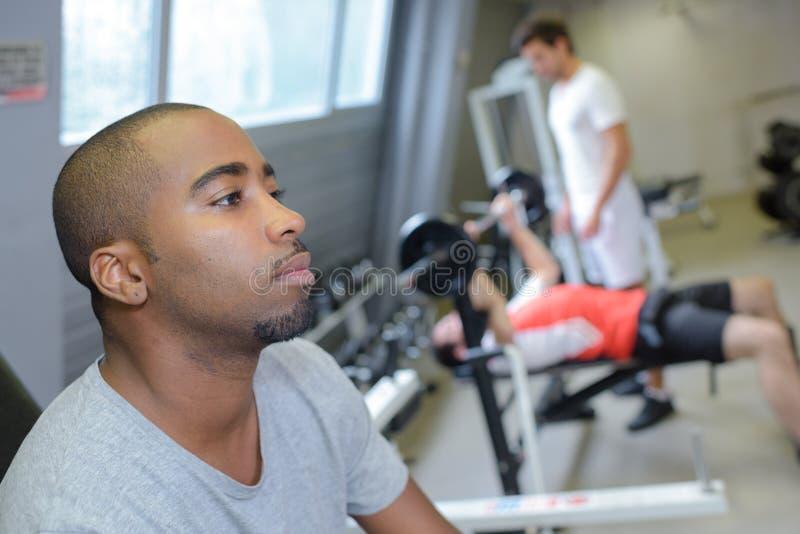 Vermoeide mens in gymnastiek stock afbeeldingen