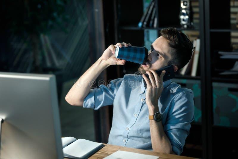 Vermoeide mens het drinken koffie in overhours royalty-vrije stock foto