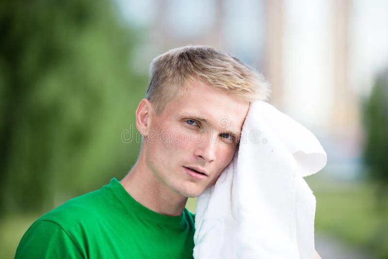 Vermoeide mens na geschiktheid tijd en het uitoefenen Met witte handdoek stock afbeelding
