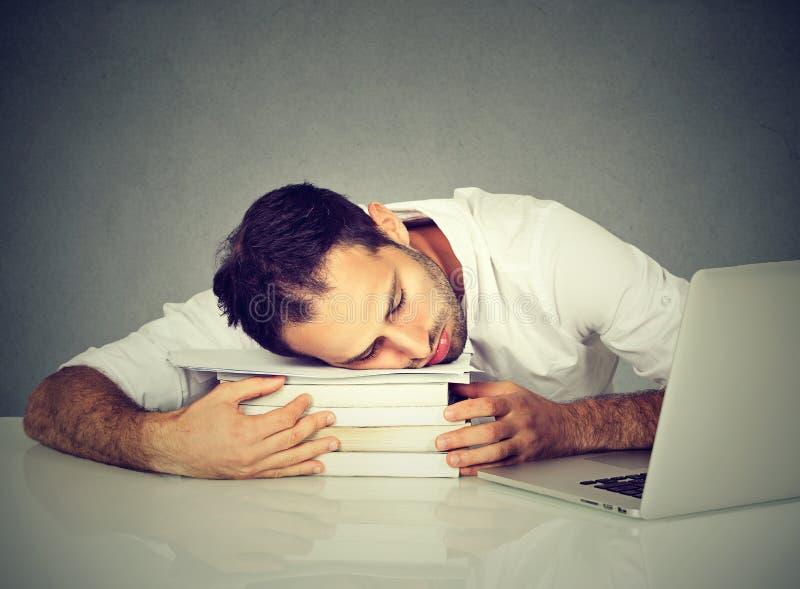 Vermoeide mensenslaap op boeken bij zijn bureau voor computer royalty-vrije stock afbeeldingen