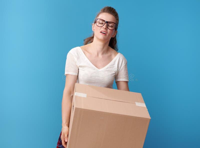 Vermoeide moderne vrouw in wit overhemd met kartondoos op blauw royalty-vrije stock afbeeldingen