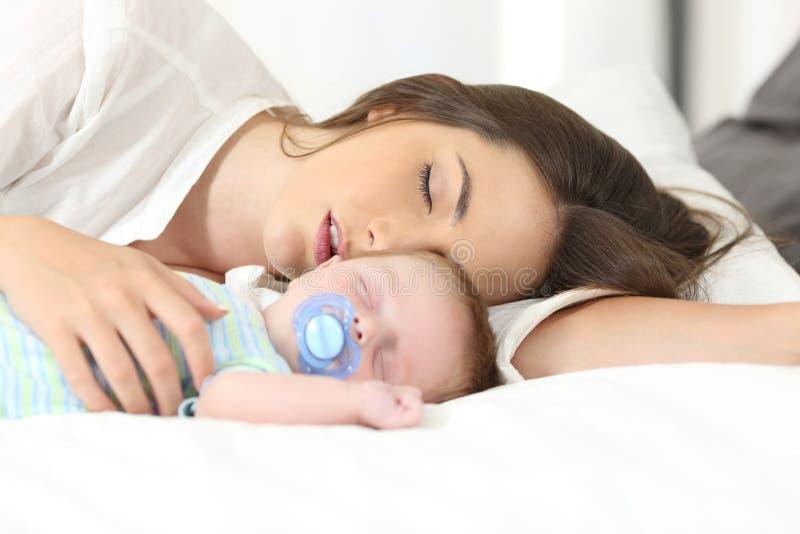 Vermoeide moederslaap met haar baby royalty-vrije stock fotografie