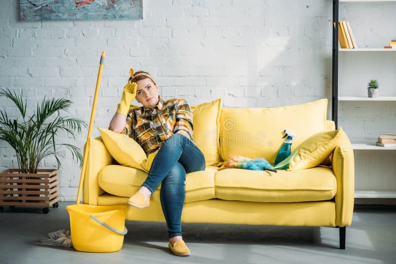 vermoeide mooie vrouwenzitting op bank na het schoonmaken stock fotografie