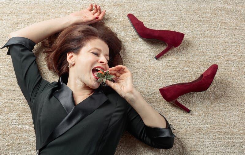 Vermoeide onderneemster die op het tapijt liggen en aardbeien eten royalty-vrije stock afbeelding