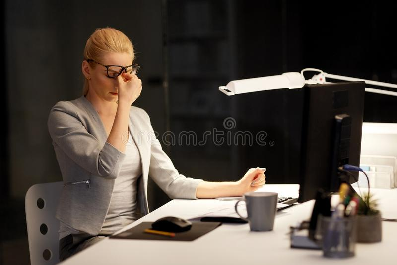 Vermoeide onderneemster die op nachtkantoor werken stock fotografie