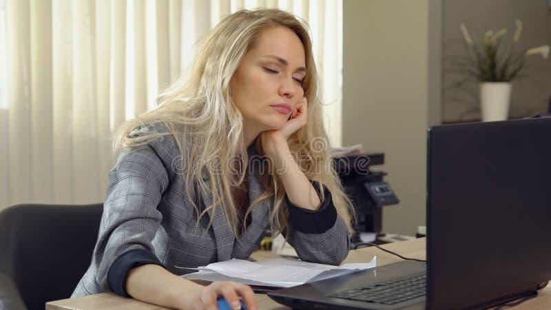 Vermoeide onderneemsterdalingen in slaap bij de werkplaats in bureau royalty-vrije stock fotografie