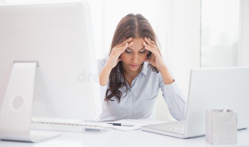Vermoeide onderneemsterzitting bij haar bureau stock foto