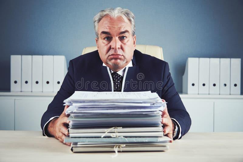 Vermoeide oude zakenman met stapel van documenten stock afbeelding