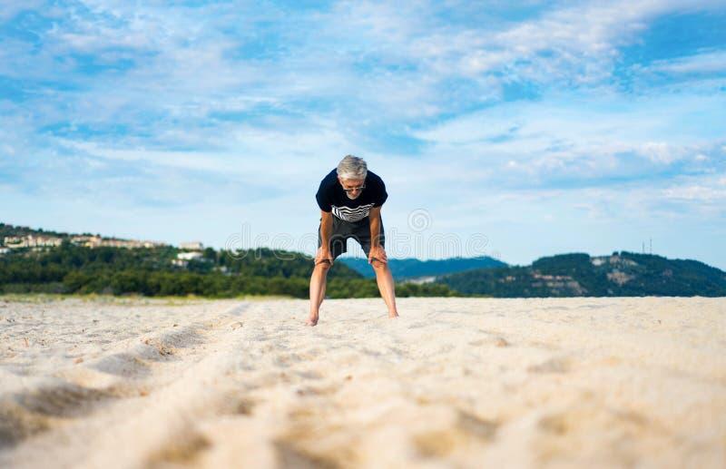 Vermoeide oudste die rust nemen tijdens oefening op het strand stock foto's