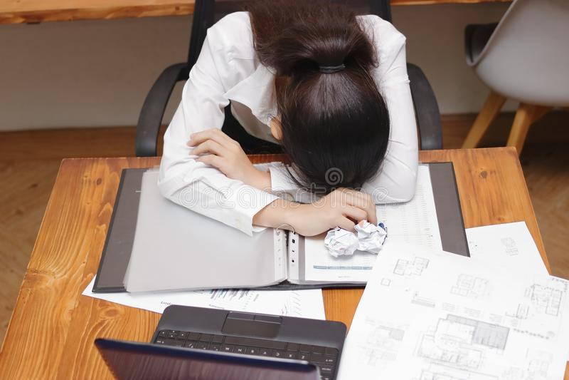 Vermoeide overwerkte jonge Aziatische bedrijfsvrouwenkromming onderaan hoofd op werkplaats in bureau stock afbeelding