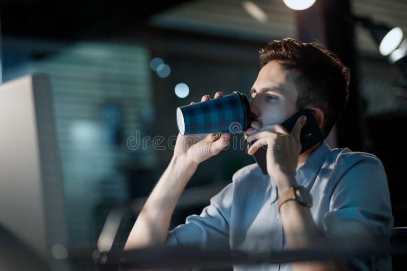 Vermoeide overwerkte mens het drinken koffie in bureau stock afbeeldingen