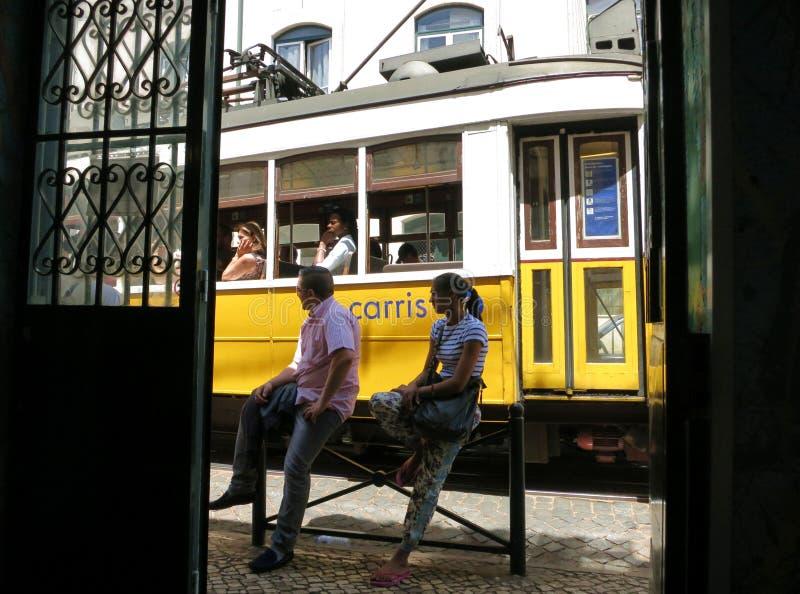 Vermoeide passagiers die op een tram in de schaduw op een hete middag wachten stock afbeeldingen