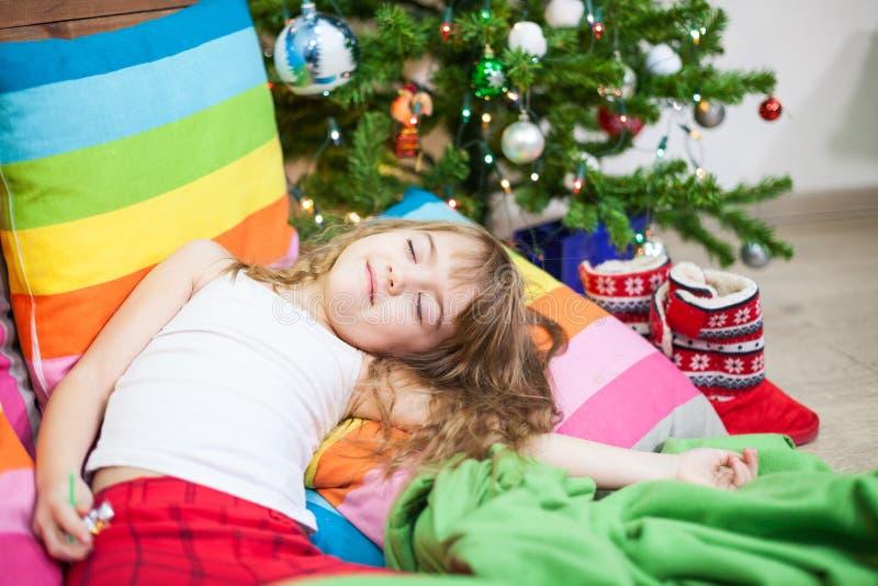 Vermoeide peutermeisjesslaap bij nacht vóór Kerstmis dichtbij groene boom stock fotografie