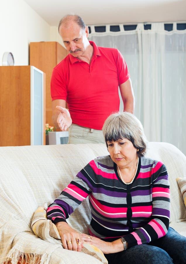 Vermoeide rijpe vrouw die aan boze echtgenoot luisteren stock afbeelding