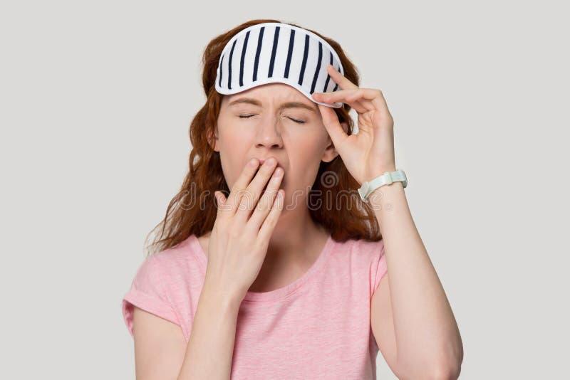 Vermoeide roodharigevrouw die de studio van het maskergeeuwen van het slaapoog headshot dragen stock afbeeldingen