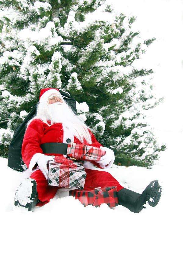 Vermoeide Santa Claus in de sneeuw stock afbeeldingen