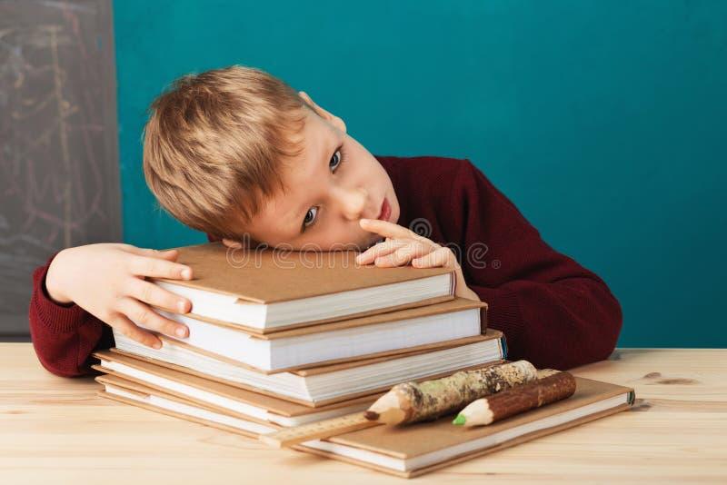Vermoeide schooljongen in slaap op boeken weinig studentenslaap op tex stock foto