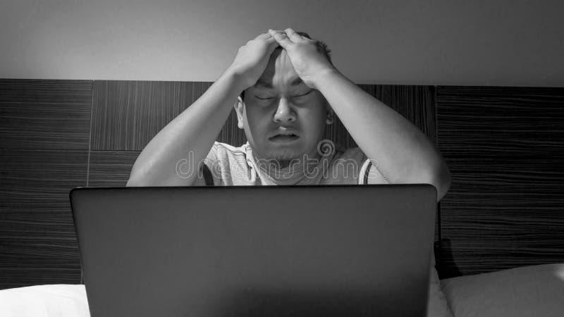 Vermoeide Slaperige Mens die aan Laptop tot Middernacht op Bed werken stock foto's