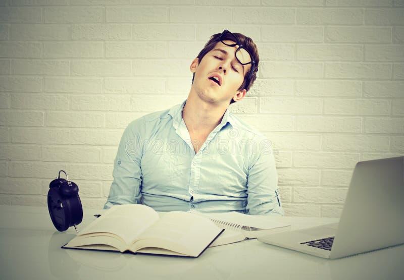 Vermoeide slaperige mensenzitting bij bureau met boeken voor laptop stock fotografie