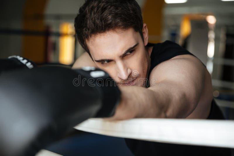 Vermoeide sportman na opleiding die op ring leunen royalty-vrije stock afbeelding