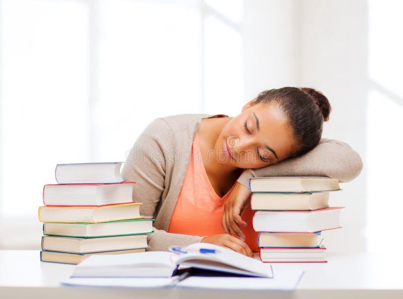 Vermoeide student met boeken en nota's royalty-vrije stock afbeeldingen
