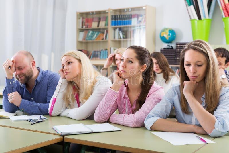 Vermoeide studenten die bij les zitten royalty-vrije stock fotografie