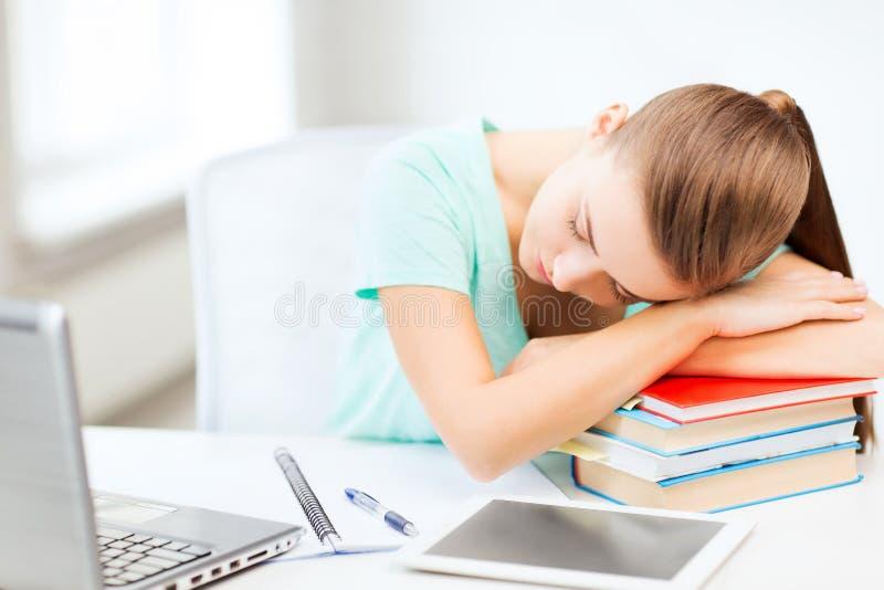 Vermoeide studentenslaap op voorraad van boeken stock fotografie