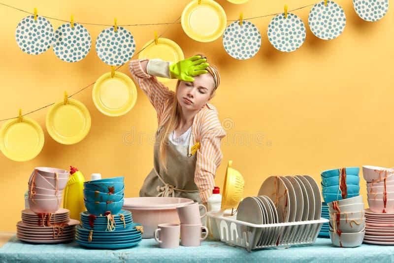 Vermoeide uitgeputte reinigingsmachine die zich in keuken en greephand bevinden op voorhoofd stock afbeeldingen