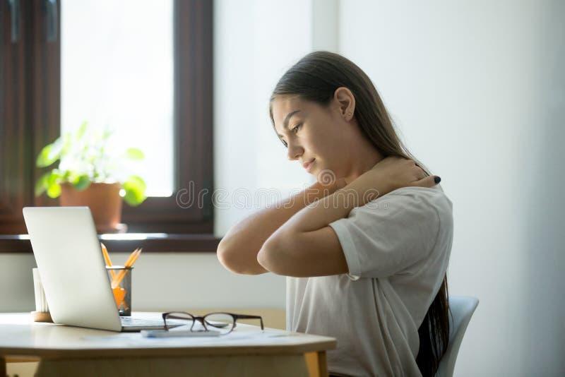 Vermoeide uitgeputte vrouwenzitting en het ontspannen in bureau stock fotografie