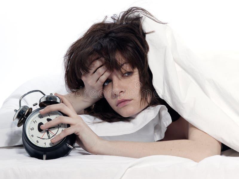 Vermoeide vrouw in bed het wekken houdend wekker stock foto's