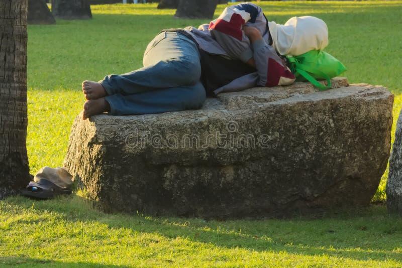 Vermoeide vrouw, die in de vroege ochtend op een harde kei in een Thais park, met behandeld gezicht slapen royalty-vrije stock afbeelding