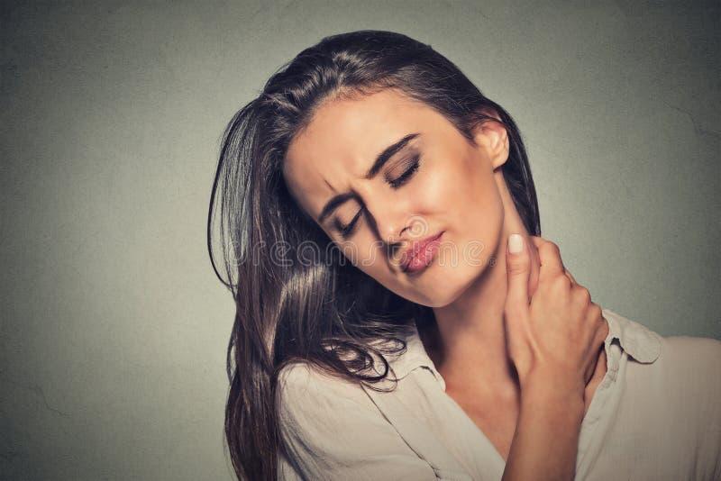 Vermoeide vrouw die haar pijnlijke hals masseren stock afbeeldingen