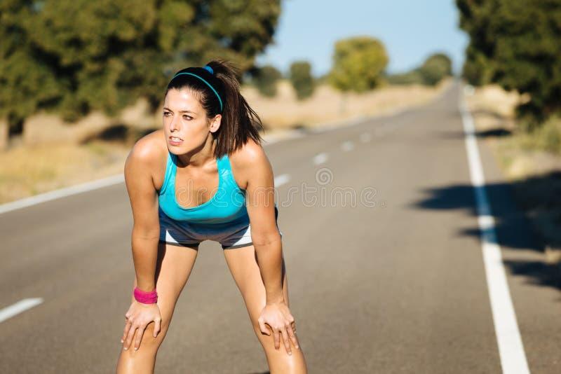Vermoeide vrouw die na het lopen op weg zweten royalty-vrije stock fotografie