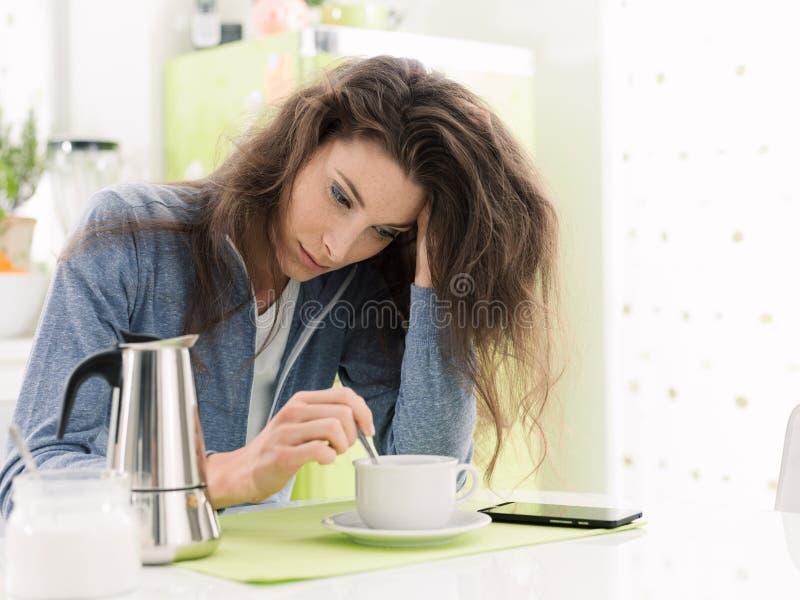 Vermoeide vrouw die ontbijt hebben thuis stock foto's