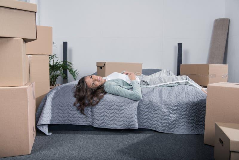 vermoeide vrouw die op bed na het uitpakken van kartondozen bij nieuw huis, het bewegen liggen zich royalty-vrije stock foto's