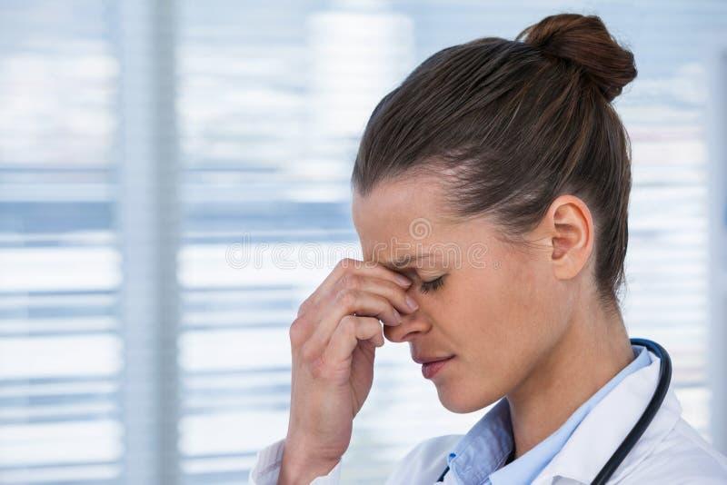 Vermoeide vrouwelijke arts die hoofdpijn hebben royalty-vrije stock fotografie