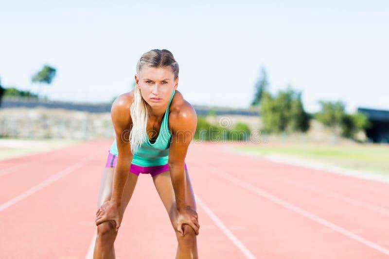 Vermoeide vrouwelijke atleet die zich op renbaan bevinden stock afbeelding