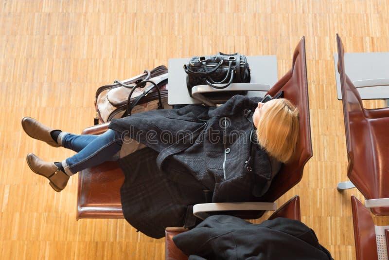 Vermoeide vrouwelijke reiziger die op vertrek wachten stock fotografie