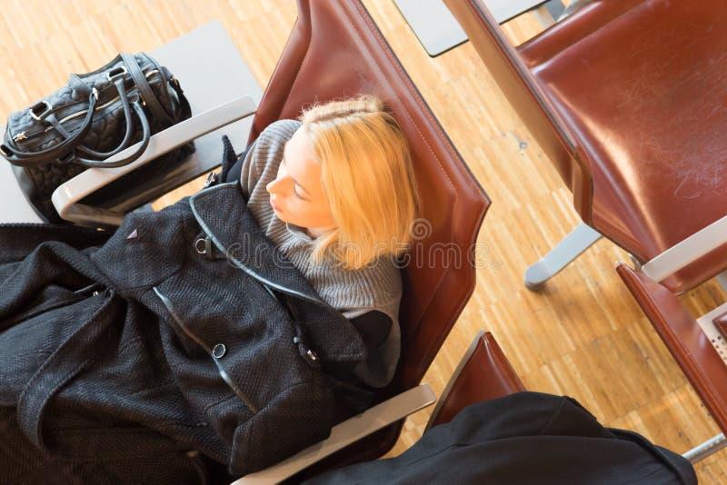 Vermoeide vrouwelijke reiziger die op vertrek wachten stock foto's