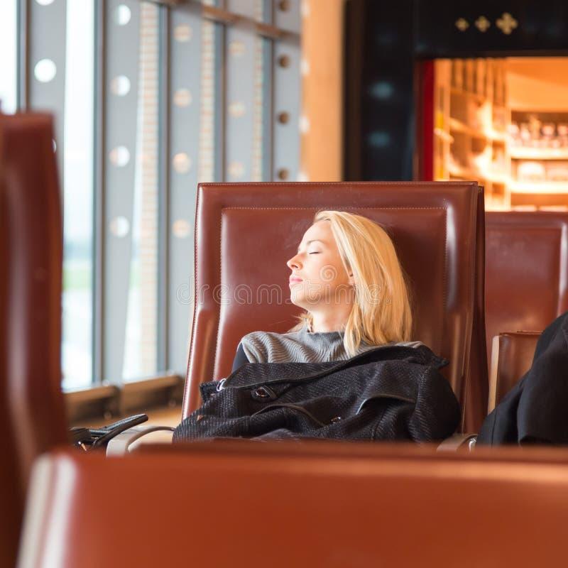 Vermoeide vrouwelijke reiziger die op vertrek wachten stock foto