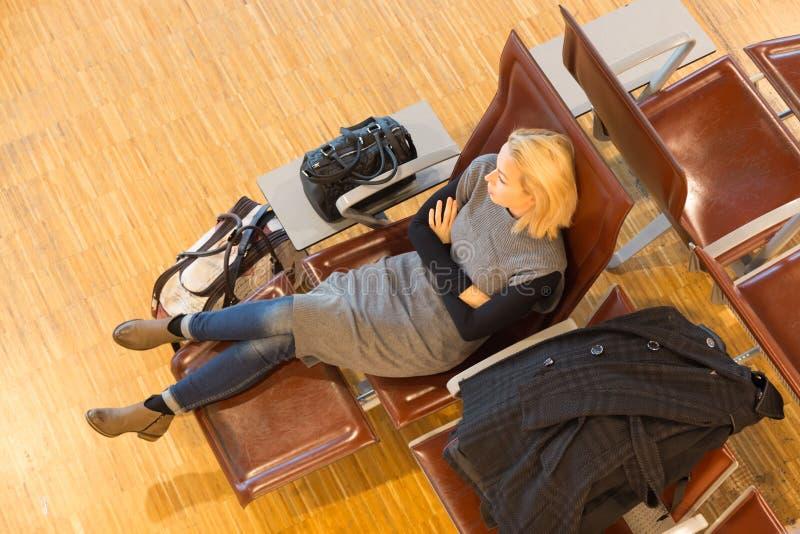 Vermoeide vrouwelijke reiziger die op vertrek wachten royalty-vrije stock afbeelding
