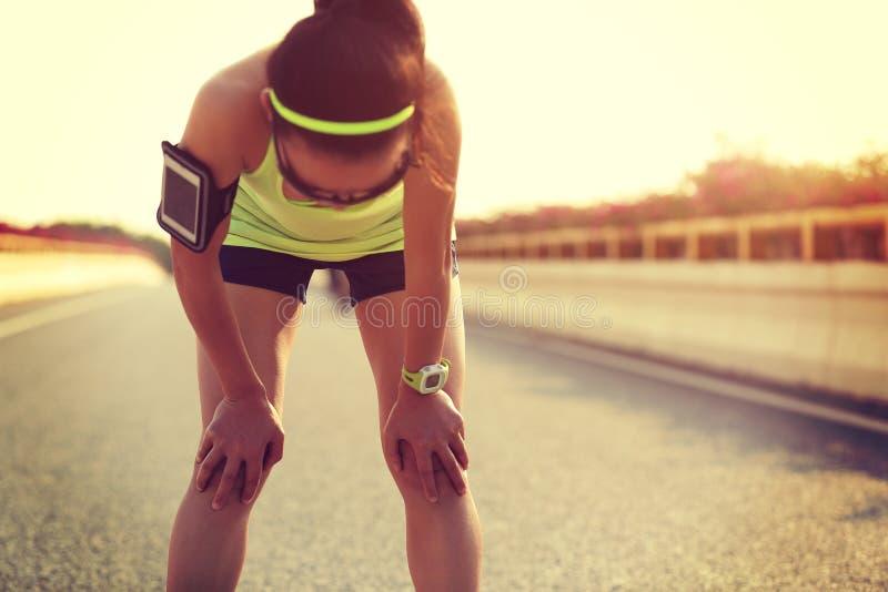 Vermoeide vrouwenagent die een rust na hard het lopen nemen stock afbeelding