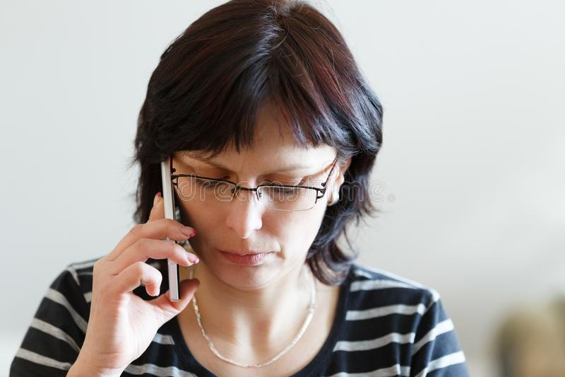 Vermoeide vrouwenvraag op middelbare leeftijd telefonisch royalty-vrije stock foto